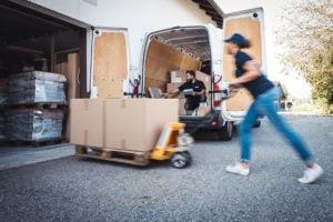 Kurier liefert Paletten mit Hubwagen